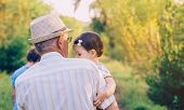 foto of senior men  - Back view of senior man holding adorable baby girl in his arms over a nature background - JPG