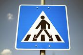 pic of pedestrian crossing  - Blue pedestrian crossing sign against blue sky - JPG