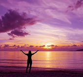 stock photo of cloudy  - girl under a pink cloudy sunset in Alghero Italy - JPG