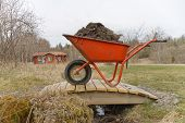 foto of hand-barrow  - Orange wheel barrow full of mud standing on a small bridge - JPG