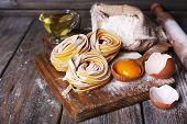 pic of pasta  - Raw homemade pasta and ingredients for pasta on wooden background - JPG