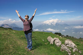 stock photo of hands up  - Photo of an active female with backpack and hands pointing to the sky while hiking up a mountain trail.