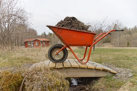 stock photo of hand-barrow  - Orange wheel barrow full of mud standing on a small bridge - JPG