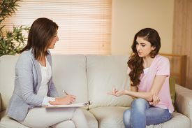 foto of therapist  - Therapist listening to her patient in therapists office - JPG