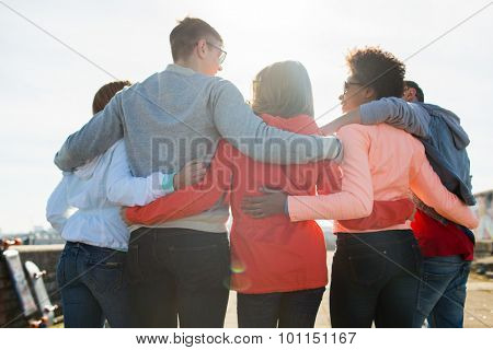 tourism, travel, people, leisure and teenage concept - group of happy friends hugging and talking on