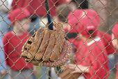 stock photo of little-league  - focus on baseball and bat with baseball players blurred in background - JPG