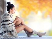 Постер, плакат: Young beautiful brunette woman with cup of coffee wearing knitted nordic print poncho sitting home