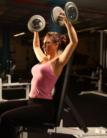 stock photo of lifting weight  - female model working out in the gym lifting weights - JPG