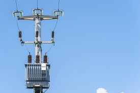 stock photo of transformer  - Electrical transformer of electrical pylon against the blue sky - JPG