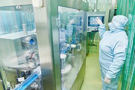 foto of pharmaceuticals  - pharmaceutical factory woman worker operating production line at pharmacy industry manufacture factory - JPG