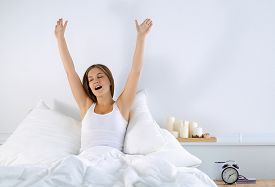 stock photo of stressless  - An attractive young woman stretching in bed after waking up - JPG