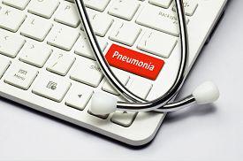 stock photo of pneumonia  - Pneumonia text stethoscope lying down on the cumputer keyboard - JPG