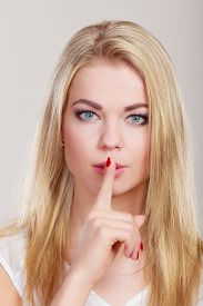 stock photo of hush  - Closeup woman asking for silence or secrecy with finger on lips hush hand gesture - JPG