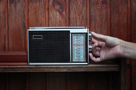 stock photo of musical scale  - Male hand tuning the old receiver with analogue scale listening news or music next to wooden wall - JPG