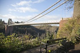 pic of suspension  - A bench seat overlooking the Clifton suspension bridge in Bristol UK built by Isambard Kingdom Brunel the bridge spans the river Avon - JPG