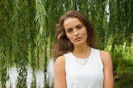 foto of weeping  - young woman wearing a white dress standing in front of a weeping willow tree in a park - JPG
