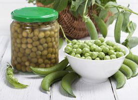 stock photo of pea  - Fresh green peas in a white bowl canned peas in a glass jar and some pea pods on a white table - JPG