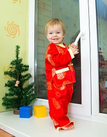 picture of new years baby  - Baby boy in Chinese new year costume stands on the window sill - JPG