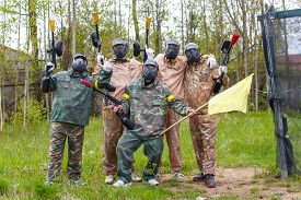 stock photo of paintball  - Team of five men with flag play paintball - JPG