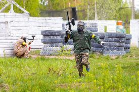 stock photo of paintball  - Man armed with paintball marker on the run - JPG