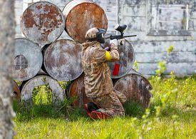 image of paintball  - Paintball sportsman in ambush behind rusty barrels - JPG