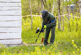 stock photo of paintball  - Paintball player outdoors in summer with marker - JPG