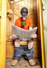 stock photo of respirator  - Man in respirator reading newspaper in wooden village WC - JPG