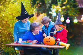 stock photo of jack o lanterns  - Family carving pumpkin at Halloween - JPG