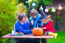 picture of jack o lanterns  - Family carving pumpkin at Halloween - JPG