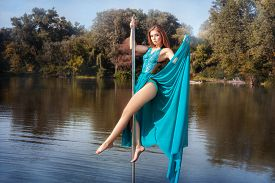 stock photo of lap dancing  - Girl in dress dancing on a pole in the lake - JPG