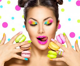 pic of lipstick  - Beauty fashion model girl with colourful makeup and manicure taking colorful macaroons - JPG