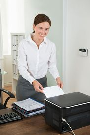 stock photo of insert  - Young Female Secretary Inserting Paper In Printer At Desk - JPG