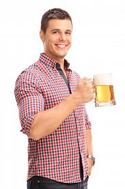 stock photo of mug shot  - Vertical shot of a cheerful young man holding a beer mug full of beer and smiling isolated on white background - JPG