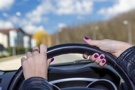 stock photo of steers  - Hands of mature female racer on steering wheel Woman holds the cars steering wheel - JPG