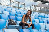 Sexy Sport Girl Posing At Stadium With The Backpack. Fitness Girl With A Sports Figure In Black Legg poster