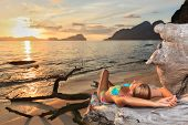 stock photo of tropical island  - Woman relaxing on the tree root at sunset time - JPG