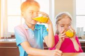 Siblings drinking orange juice in kitchen at home poster