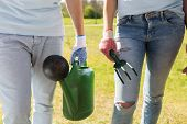 volunteering, people and gardening concept - couple of volunteers with watering can and weeding rake poster
