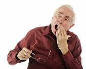 picture of bifocals  - A weary senior man with a big yawn - JPG