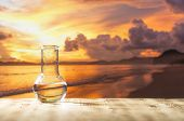 Clean water in a glass laboratory flask on wooden table on sunset background. Ecological concept, th poster