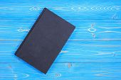 Old Black Book On Wooden Plank Background. Blank Empty Cover For Design poster