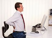 Man in office with computer and back pain