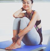 Portrait of smiling yoga woman sitting at yoga mat after workout at yoga studio. Yoga. Woman. poster