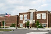 foto of school building  - Red brick school building with American flag waving - JPG