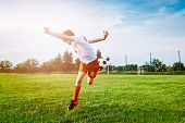 Boy Playing With Football Ball On Playing Field. poster