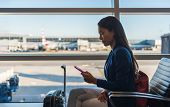 Airport phone travel woman using mobile phone in business class lounge waiting for plane flight text poster