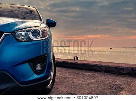 poster of Blue Compact Suv Car With Sport And Modern Design Parked On Concrete Road By The Sea At Sunset In Th