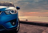 Blue Compact Suv Car With Sport And Modern Design Parked On Concrete Road By The Sea At Sunset In Th poster