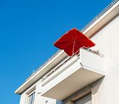 Low Angle View Of White Modern Balcony With Red Umbrella Sunshade At A Luxury Real Estate Penthouse- poster