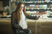Vape Teenager. Portrait Of Young Cute Girl In Sunglasses Smoking An Electronic Cigarette In Vape Bar poster